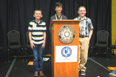 The top three contestants in the Washington State Geographic Bee pose after the conclusion of the finals. From left are fourth grader Jacob Krell (second place), eighth grader Nick Harrington (first place), and seventh grader Evan Scavotto (third place). (Photo by Kyle Haddad-Fonda)