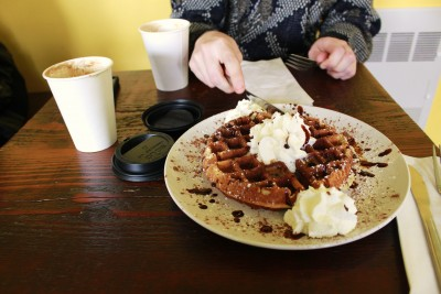 The waffle iron at Cortona Café is hot and ready to make fluffy Belgian or vegan waffles. Pictured is the house staple, a tiramisu waffle (Photo by Brie Ripley).