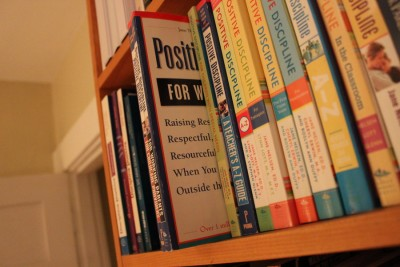 """In Dr. Jody McVitties's book shelf, Jane Nelson's guide """"Positive Discipline"""" is accompanied by books like """"Raising Boys"""" and """"White Awareness (Photo by Agazit Afeworki)"""