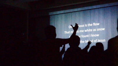 Students lift their hands as they sing worship songs. (Photo by Monica Chon)