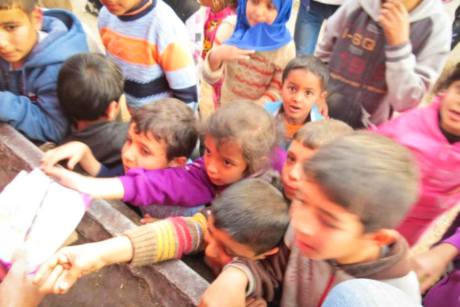 Children in a camp for Syrian refugees clamor for aid distributed by SACCWA. (Courtesy photo)