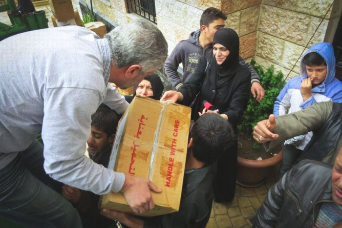 """Bashar Kabor (left) distributing essential supplies in Erbid, Jordan in April 2013. Kabor said the contrast between life for Syrian refugees and his life in Seattle is a shock that's hard to get used to. """"Everytime we get back, we're depressed,"""" Kabor said of his organization's missions. """"It takes a few weeks for us to recover from those trips."""" (Photo courtesy of Bashar Kabor)"""