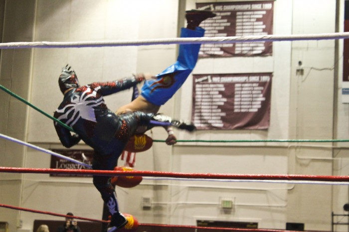 El Heroe delivers a kick as Ave Rex somersaults over him (Photo by Olivia Fuller).