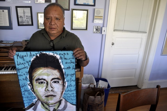 Estanislao Mendoza Chocolate at Immanuel Lutheran Church in Seattle with a portrait of his missing son, Miguel Ángel Mendoza Zacarías. (Photo by Janelle Retka)