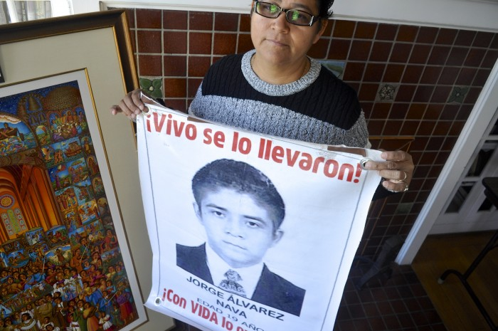 "Blanca Luz Nava Vélez holds a poster of her missing son, Jorge Alvarez Nava, which reads ""They took him alive!"" (Photo by Janelle Retka)"