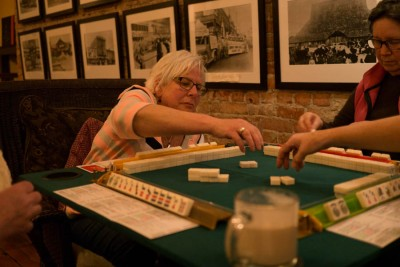 Doreen Zemble, a member of Mah Jongg Fever is picking the tile during the game. (Photo from the Seattle Globalist by Yiqin Weng)