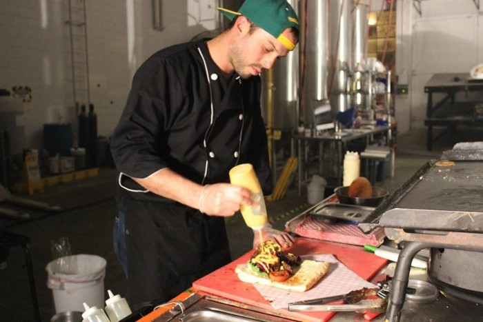 Chalisea applies the finishing touches to a Lomo Saltado Sandwich. (Photo by Cristy Acuña)