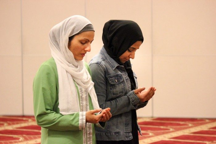Aneelah Afzali (left) and her friend, Roya Jalili, pray at the Muslim Association of Puget Sound (MAPS) mosque in Redmond. (Photo by Ashley Walls.)