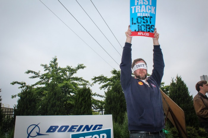 Garett Scott, a letter carrier and member of the AFL-CIO, pickets before a visit by Secretary of State John Kerry at the Boeing Co.'s Renton plant. (Photo by Venice Buhain.)