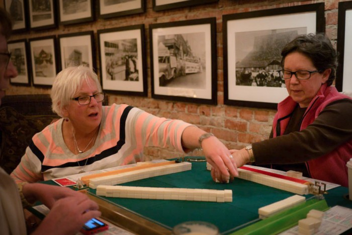 Doreen Zemble and Linda Dupuis-Fricke, both the members of Mah Jongg Fever, are exchanging tiles during the game. (Photo from the Seattle Globalist by Yiqin Weng)