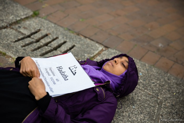 Fethya Ibrahim, a junior at UW, participates in a die-in on Red Square representing the depopulated Palestinian village Hadatha. Each of about 50 participating students had a similar sign with the name of a depopulated Palestinian village written in English and Arabic. (Photo by Aditya Ganapathiraju)