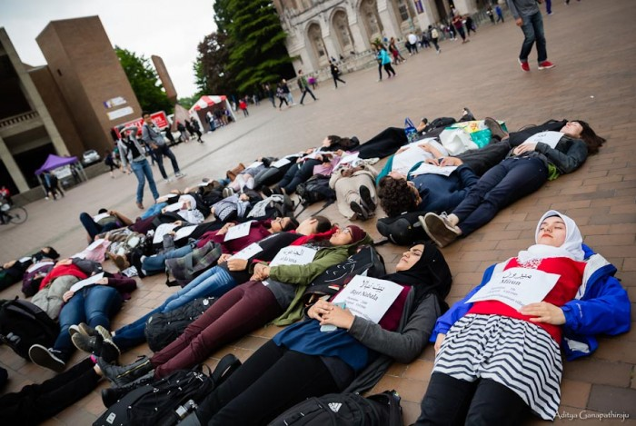 Senior Meva Beganovic, sophomore Rabbia Pasha and senior Yasmeen Samad (right to left) lie silently among the sea of die-in protestors, while students passing by on their way to classes look on. (Photo by Aditya Ganapathiraju)