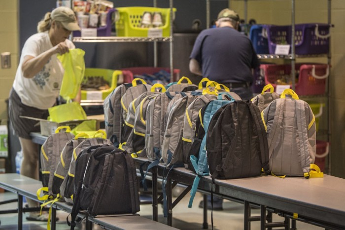 Volunteers Joann Wittler, left in backround and Larry Hill load up bags of donated food that are stuffed into backpacks for 64 studenta at Thorndyke Elementary School for weekend meals. (Photo by Steve Ringman/The Seattle Times)
