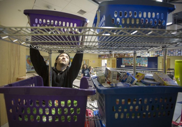 Volunteer Kevin Tran stacks bins of donated food for weekend backpacks for 64 students at Thorndyke Elementary school in Tukwila. (Steve Ringman/The Seattle Times)