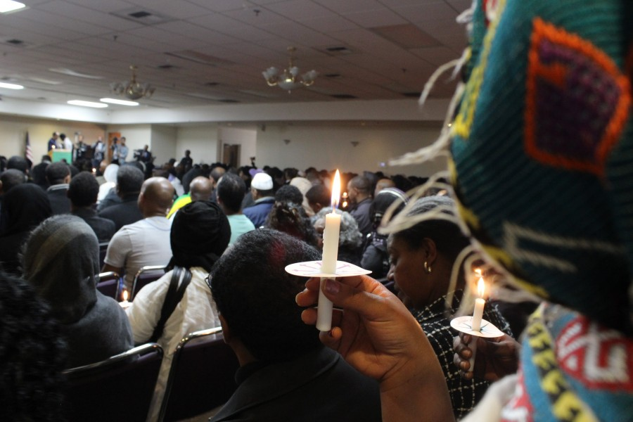 An Ethiopian woman at her community center holds a candle in remembrance for the Christians killed by ISIS Center. (Photo by Agazit Afeworki for the South Seattle Emerald.)