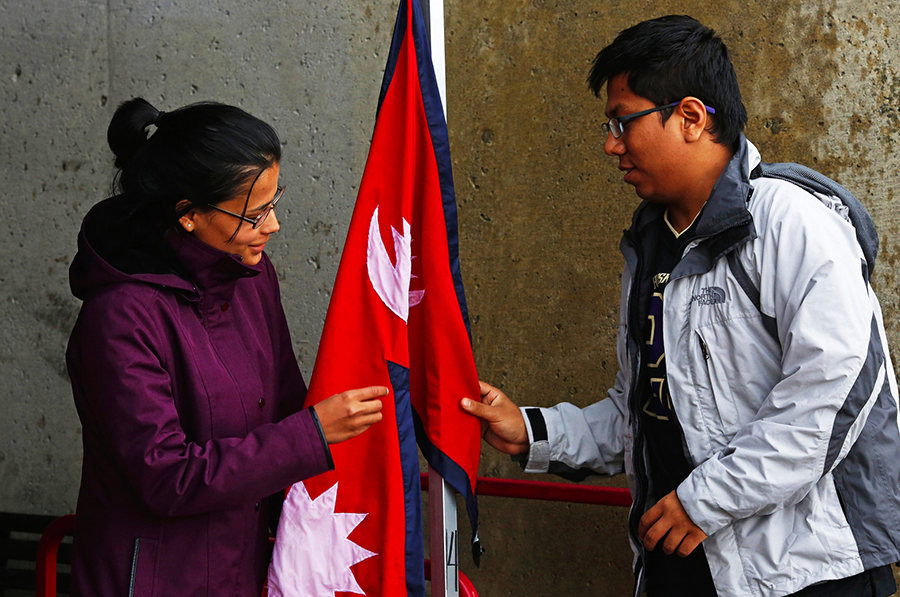 Krishna Rizal, at left, and Prerak Pradhan hang a Nepali flag at their fundraising booth on Red Square at the University of Washington on Tuesday May 5, 2015. Students and faculty on the UW campus are challenging themselves to raise $50,000 to go directly to rebuilding Simjung which was the town closest to last week's earthquake in Nepal