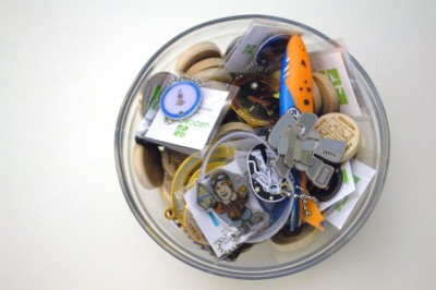 A bowl of geocoins and travel tags sits on the desk of a Geocaching.com Lackey at Geocaching headquarters in Fremont. (Photo by Joanna M. Kresge)