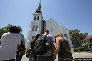 Mourners pay their respects outside Emanuel African Methodist Episcopal Church after the street was re-opened a day after a mass shooting left nine dead during a bible study at the church in Charleston, South Carolina June 18, 2015. REUTERS/Brian Snyder