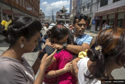 Local residents comfort each others during an earthquake in central Kathmandu, Nepal, May 12, 2015. (Photo from REUTERS/Athit Perawongmetha)