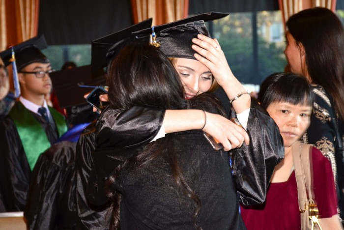 Nino Chaboshvili is congratulated by her best friend on being among the first graduates from the Seattle World School. (Photo by Valeria Koulikova.)