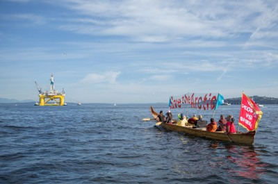 Native Activists in a canoe follow Shell's Polar Pioneer drilling rig out of Elliott Bay in June. (Photo by Alex Garland)