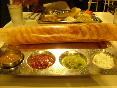 Photo of a dosa served with sambar and chutney.(photo via saravana bhavan.com)