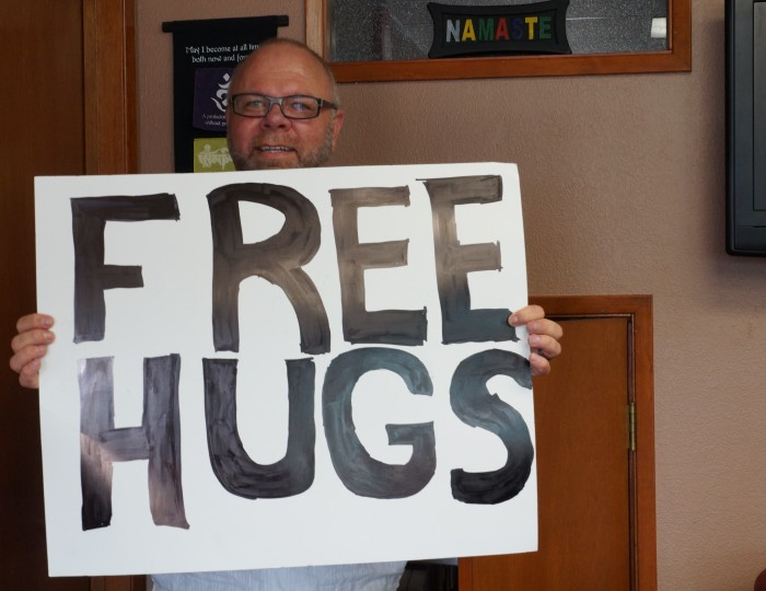 Rev. Mosley shows a banner for free hugs used by volunteers at their community service projects.