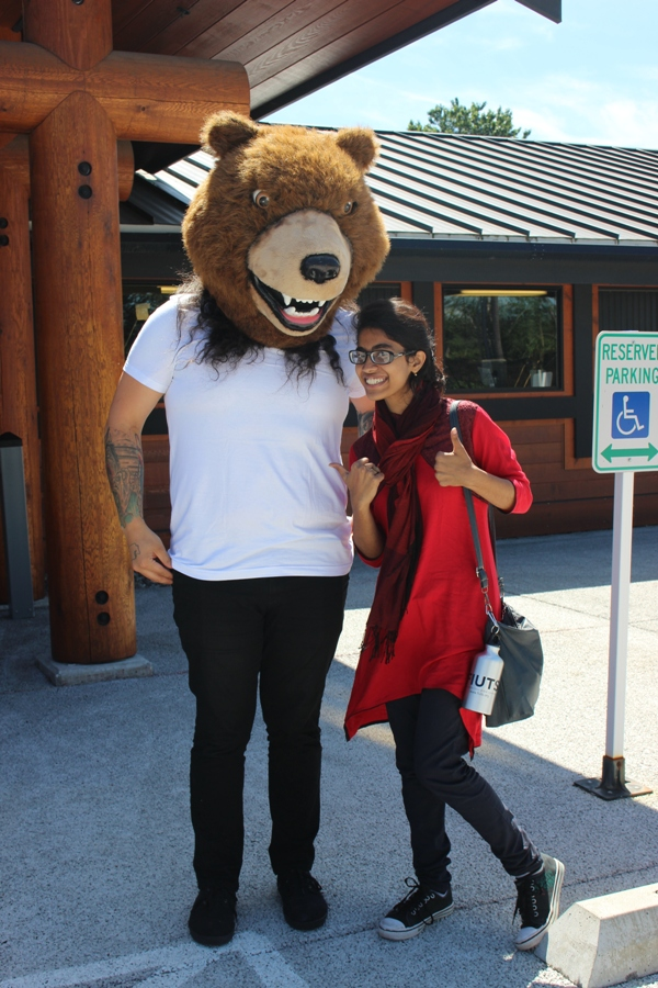 Chris in part of a bear costume used as a prop in their skits, posing for a picture with an exchange student from South Asia. Photo by Aisha Nazim.