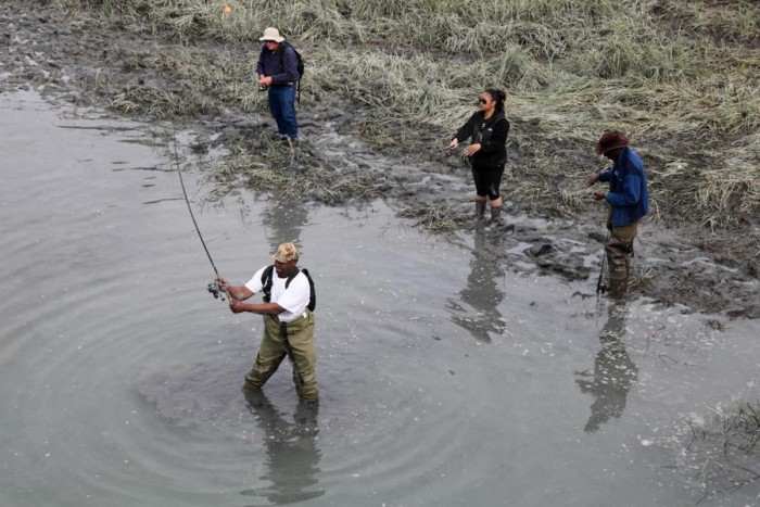 Sport fishermen angle for Silver Salmon in Ship Creek Inlet, in downtown Anchorage. (Photo by Alex Stonehill.)