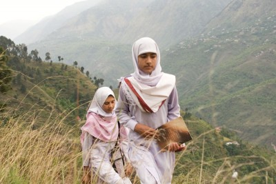 Humiera Kausar, left, and classmate Salaf walk to a school in the mountains of Kashmir that was built with funds raised in Seattle. (Photo by Alex Stonehill)