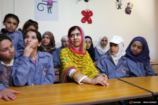Nobel Peace Prize laureate Malala Yousafzai (center) sits with girls inside a classroom at a school for Syrian refugee girls, built by the NGO Kayany Foundation, in Lebanon's Bekaa Valley on July 12th. (Photo from Reuters / Jamal Saidi)