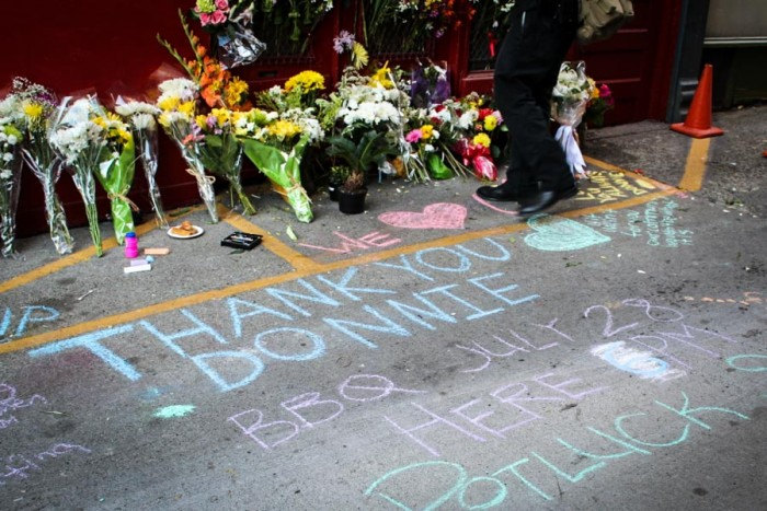 Mourners wrote messages in chalk in tribute to Donnie Chin, who was fatally shot in his car early July 23. (Photo by Venice Buhain.)