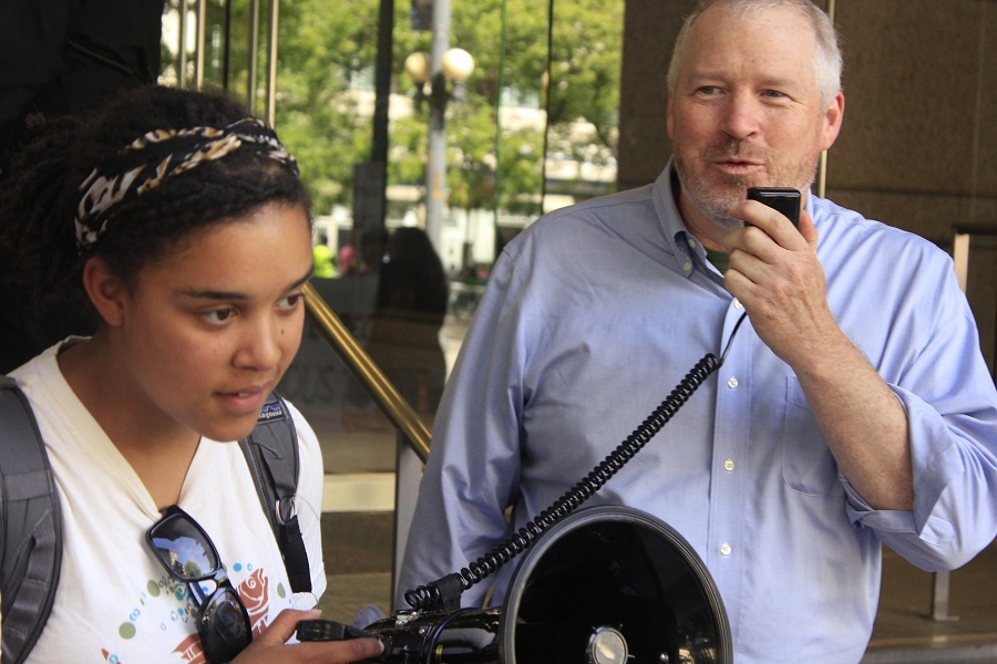 Former Seattle mayor Mike McGinn (right) addresses crowd at the entrance of the Canadian Consulate office building on Fourth Avenue in downtown Seattle. Sarra Tekola (left) is one of the organizers of the rally. (Photo by Goorish Wibneh)