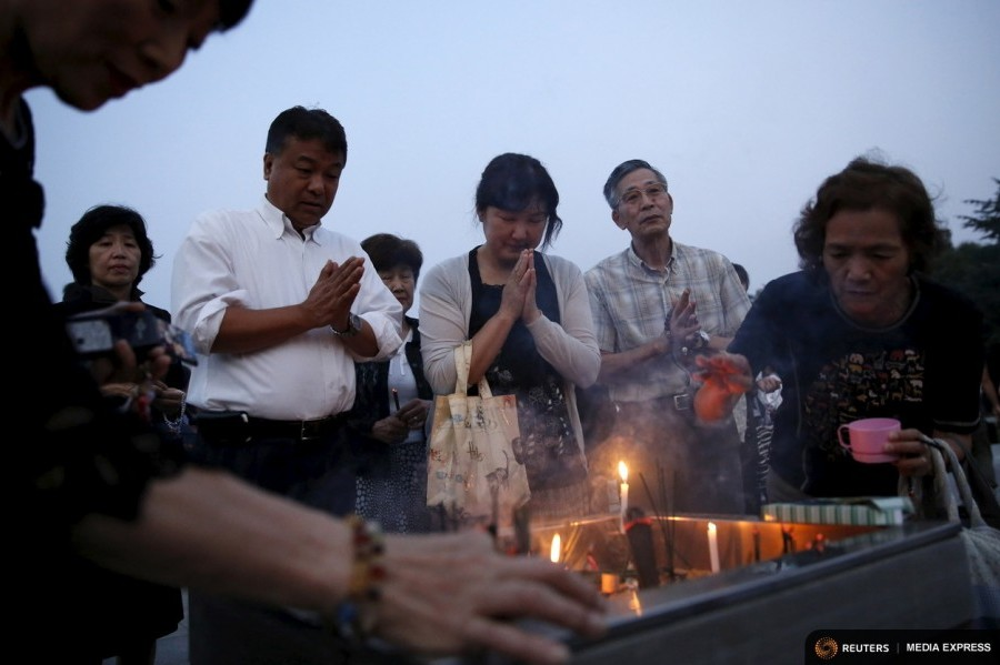 People pray for the atomic bomb victims in front of the cenotaph for the victims of the 1945 atomic bombing, at Peace Memorial Park in Hiroshima, western Japan, August 6, 2015, on the 70th anniversary of the world's first atomic bombing of the city.  Photo by Toru Hanai for Reuters.