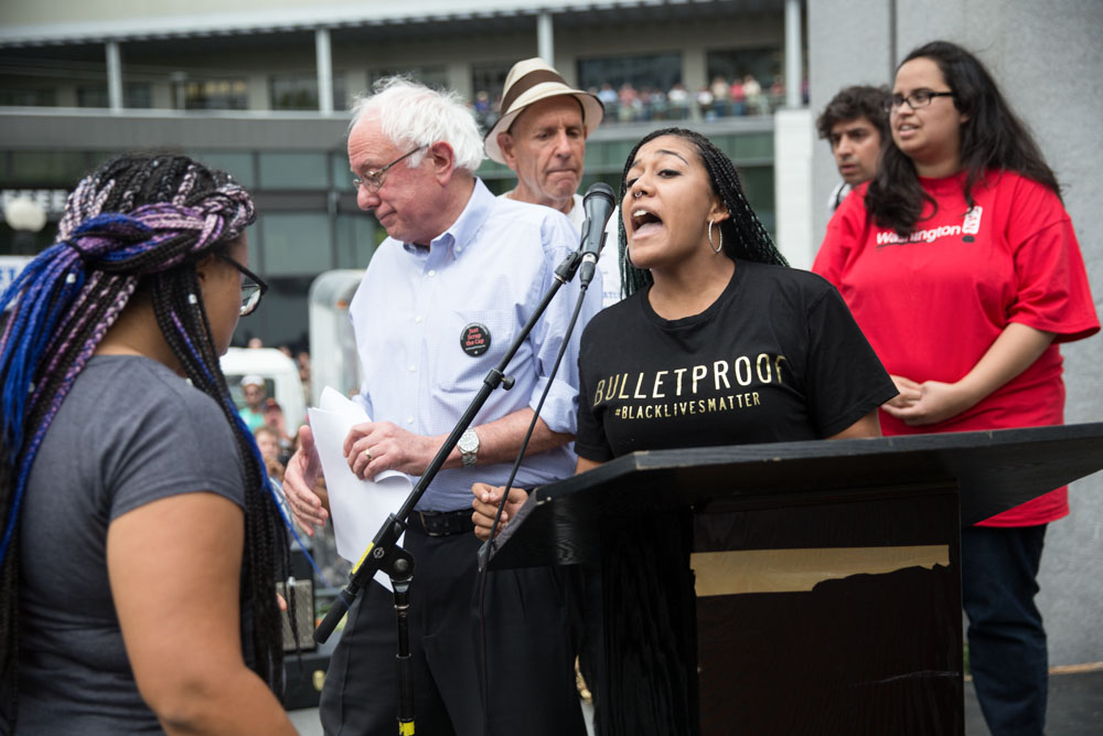 Presidential candidate Bernie Sanders walked away from the microphone as activists Mara Jacqueline Willaford and Marissa Johnson disrupted a rally at Westlake Center on Saturday where he was scheduled to speak about Social Security. (Photo by Alex Garland)