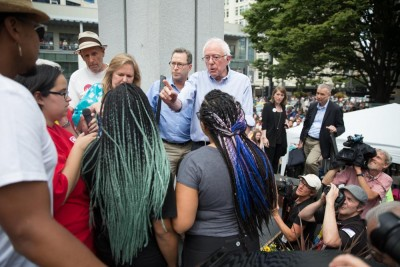 Presidential candidate Bernie Sanders talks to Black Lives Matter activists Mara Jacqueline Willaford and Marissa Johnson after they disrupted a rally at Westlake Center on Saturday where he was schedule to speak about Social Security. (Photo by Alex Garland)