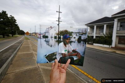 Photographer Carlos Barria holds up a print of a photograph he took after Hurricane Katrina in the same location 10 years later. The storm was early evidence of how climate change disproportionately impacts the poor and people of color. (Photo from REUTERS/Carlos Barria)