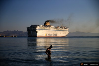 """A migrant washes as the passenger ship """"Eleftherios Venizelos"""" leaves the port on the Greek island of Kos. The passenger ship carrying Syrian refugees set sail from the Greek island of Kos in mid-August, heading for the mainland as authorities struggle to cope with a wave of arrivals. (Photo from REUTERS/Alkis Konstantinidis)"""