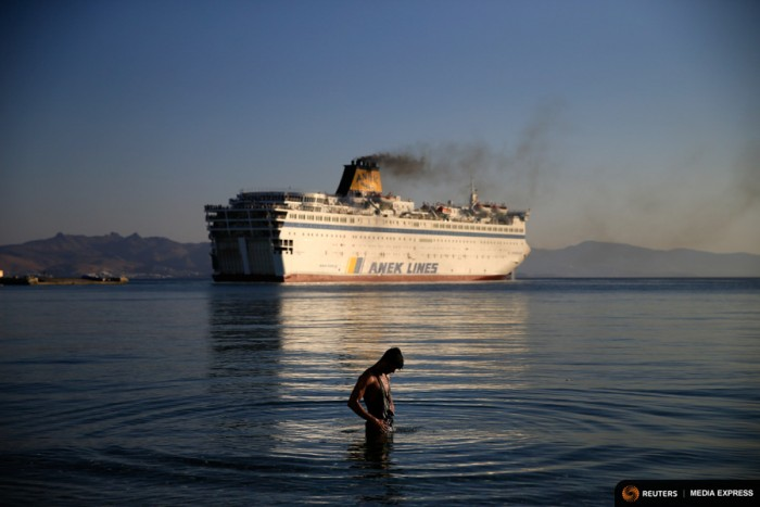 "A migrant washes as the passenger ship ""Eleftherios Venizelos"" leaves the port on the Greek island of Kos. The passenger ship carrying Syrian refugees set sail from the Greek island of Kos in mid-August, heading for the mainland as authorities struggle to cope with a wave of arrivals. (Photo from REUTERS/Alkis Konstantinidis)"