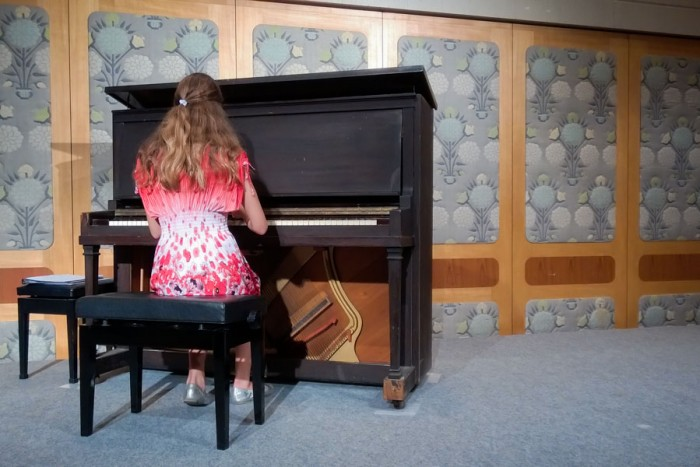 Amy Pottharst, 12, plays a piano that survived the Hiroshima bombing and was later restored. (Photo by Ed Pottharst)