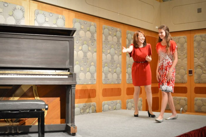Japanese singer Nana Kono shows Seattle teen pianist Amy Pottharst to the stage during a goodwill concert commemorating the 70th anniversary of the Hiroshima Bombing. (Photo by Shiori Usui)