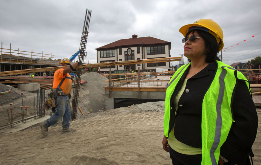 Estela Ortega, executive director of El Centro de la Raza, stands in front of one of the two buildings going up as part of a new affordable housing project on Beacon Hill. (Photo by Ellen M. Banner / The Seattle Times)