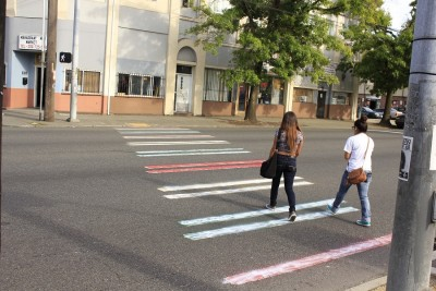 School girls crossing a a white muddled red, yellow, green painted crosswalk East-bound(Photo by Goorish Wibneh)