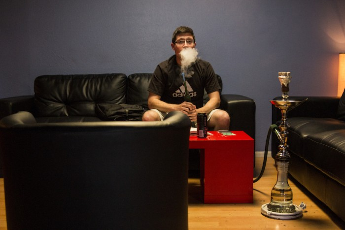 Michael Perez puffs from a shisha at Cloud 9, a hookah lounge in Seattle's Central District. (Photo by Jama Abdirahman)