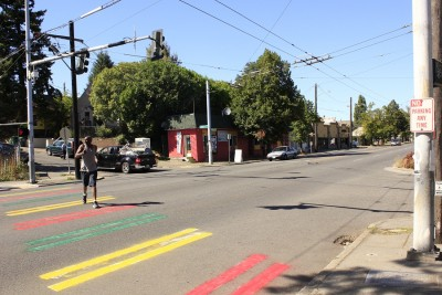 A man jaywalks on a crosswalk that has been painted green, yellow, and red for the second Tuesday after the first Ethiopian color makeover from Monday was muddled with white. (Photo by Goorish Wibneh)