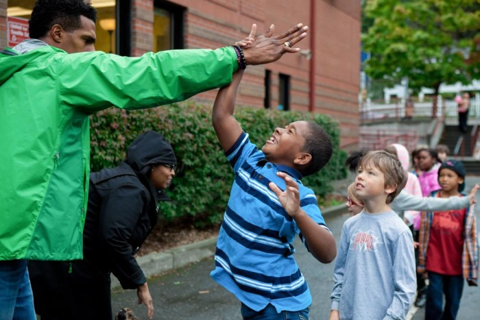 Gabriel Rapier (left) high fives a student at Leschi Elementary School on Friday, as part of #SeattleHigh5. The event aimed to show children of color positive images of black men and women in their community. (Photo by Jovelle Tamayo)