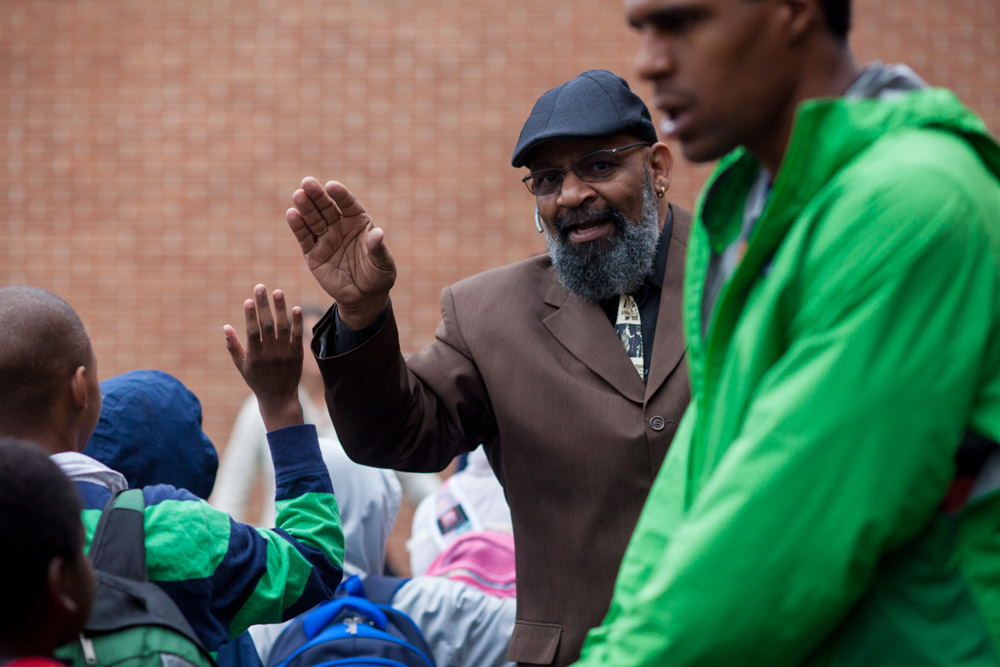 Gerald Donaldson, a Family Support Worker at Leschi Elementary School, high fives students entering the school. (Photo by Jovelle Tamayo)