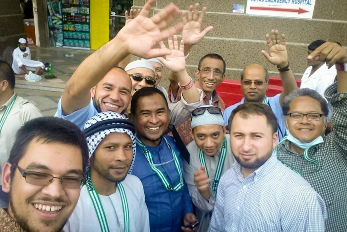 The author (lower left) with other members of the Hajj group from Washington state that he travelled with. Mohamad Joban, Imam of the Muslim Association of Puget Sound is at center in dark blue. (Photo by Tariq Yusuf)