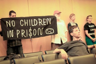 Members of anti-racist group holding a sign at the City Council committee hearing on Wednesday. (Photo by Goorish Wibneh)