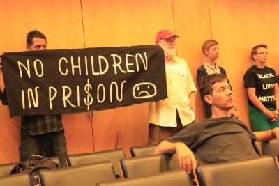 Members of anti-racist groups holding signs at the City Council committee hearing.(Photo by Goorish Wibneh)